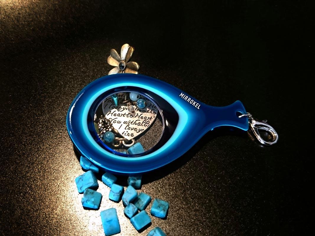 Bilden visar Mirrokel Model Blue på ett svart bord, med små blåa stenar.